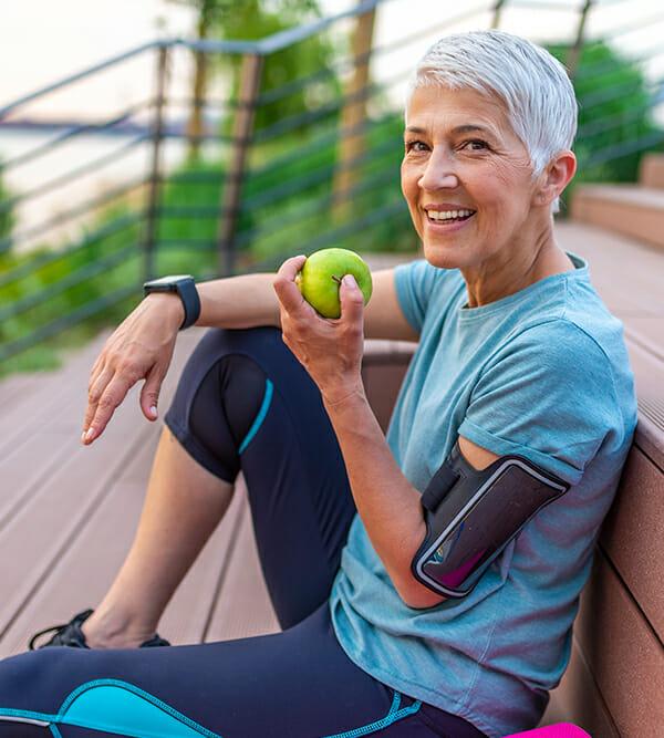 Ältere Frau isst einen Apfel